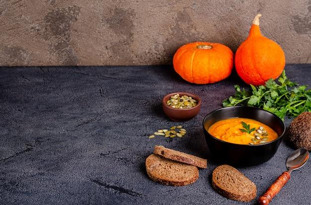 Minestra vegetariana di crema autunnale di zucche e carote con semi e prezzemolo su un tavolo scuro