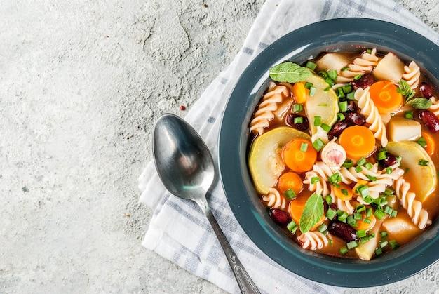 Minestrone di verdure italiano con pasta di fusilli, concetto di cibo vegetariano