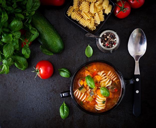 Minestrone, zuppa di verdure italiana con pasta su sfondo nero.