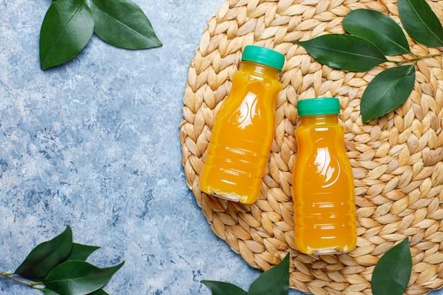 Mini bottiglie di plastica di succo d'arancia fresco biologico con arance e mandarini crudi