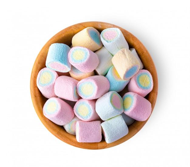 Mini caramelle gommosa e molle variopinte in ciotola di legno sulla parete bianca.