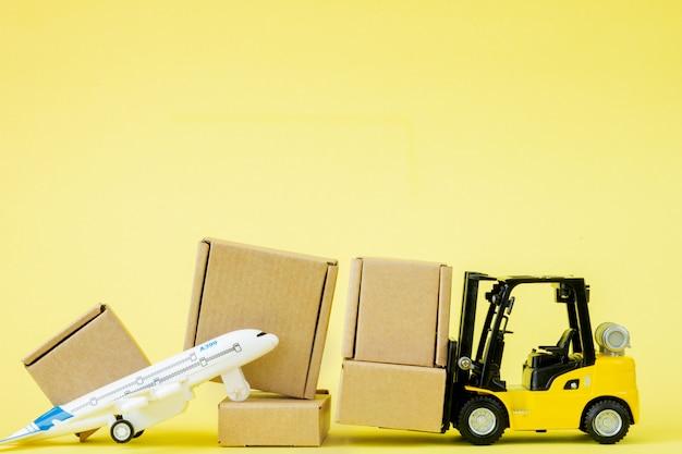 Mini carrello elevatore a forcale caricare scatole di cartone nell'aereo.