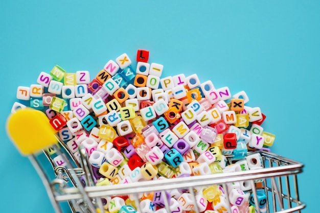 Mini carrello o carrello pieno di perle di lettera inglese su sfondo blu