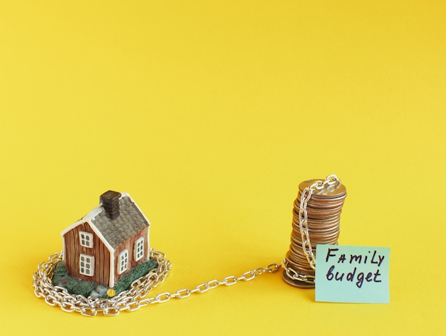 Mini casa gialla è avvolta in catena.