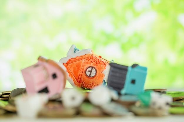 Mini casa sul mucchio delle monete con sfuocatura verde.