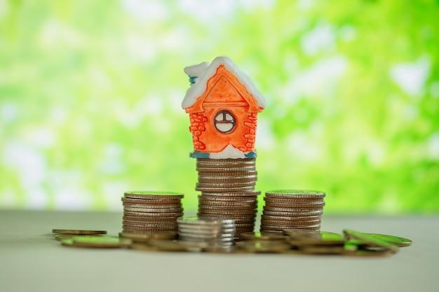 Mini casa sulla pila di monete con sfuocatura verde.