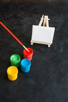 Mini cavalletto vuoto con contenitori di vernice e pennello su sfondo nero con texture