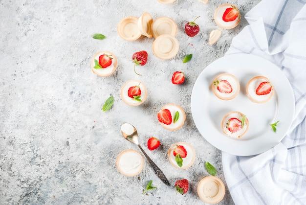 Mini cheesecakes dessert fatti in casa dolce estate con fragola sul tavolo di pietra grigia