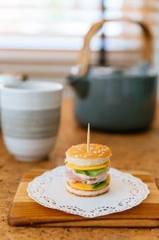 Mini chicken burger sul tagliere di legno con sfocatura tazza di tè e tazza in background.