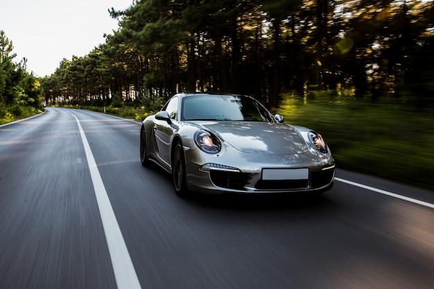 Mini coupé ad alta velocità su strada con luci anteriori accese.