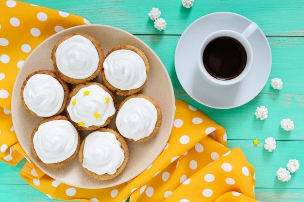 Mini crostata con crema di aria su un piatto e una tazza di caffè