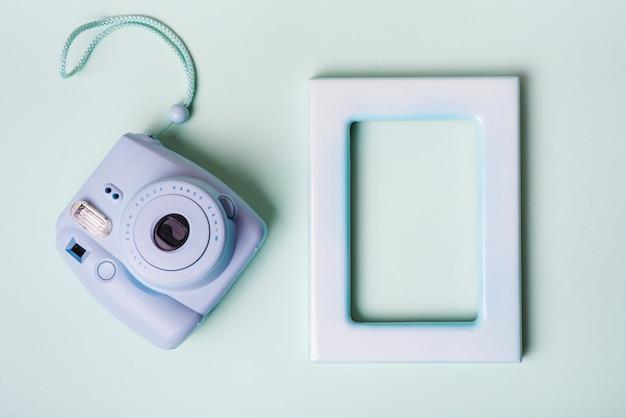 Mini macchina fotografica istantanea e cornice vuota bordo su sfondo blu