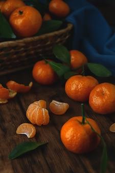 Mini mandarini con le foglie in un canestro e su una tavola di legno.