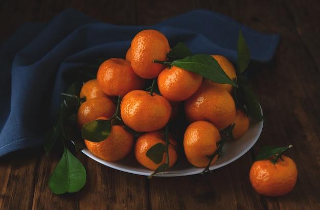 Mini mandarini con le foglie in un piatto su una tavola di legno.