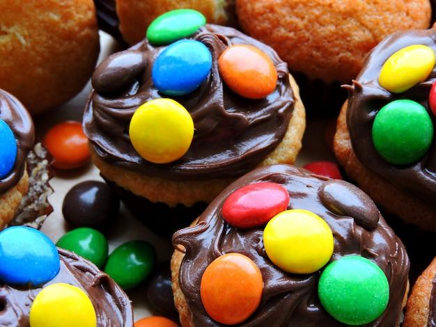 Mini muffin con topping di crema al cioccolato e caramelle colorate.