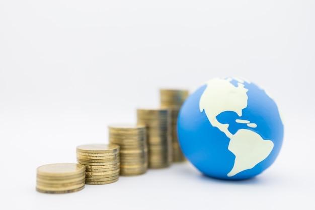 Mini palla del mondo con la pila di monete d'oro su sfondo bianco