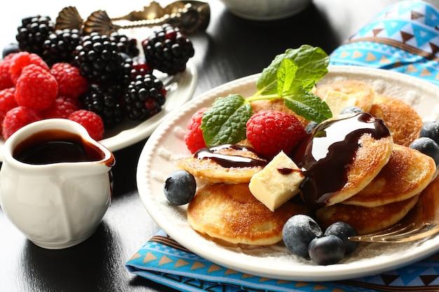 Mini pancakes olandesi chiamati poffertjes con frutti di bosco e salsa di cioccolato