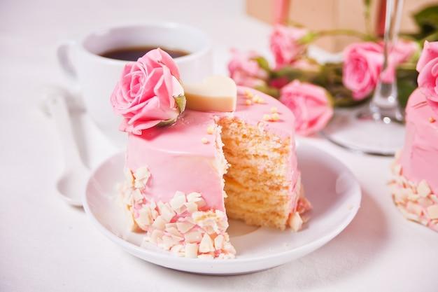 Mini piccola torta con glassa rosa, bellissime rose, tazza di caffè, confezione regalo sul tavolo bianco.
