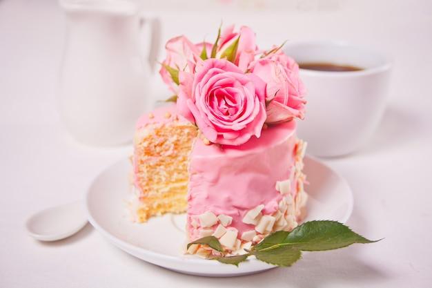 Mini piccola torta con glassa rosa, bellissime rose, tazza di caffè sul tavolo bianco.