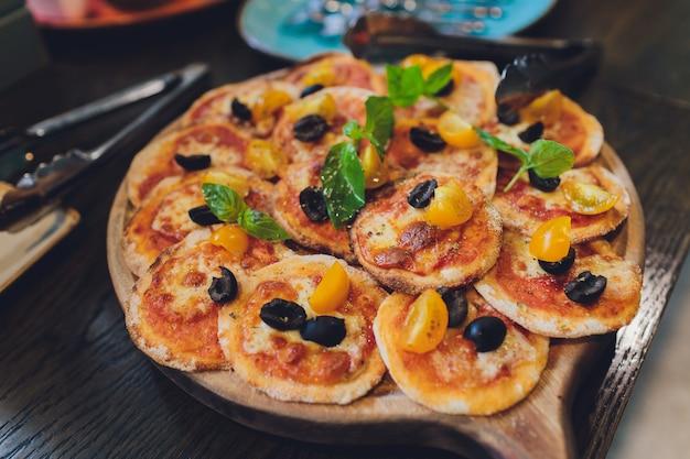 Mini pizze di pomodoro e mozzarella a bordo.