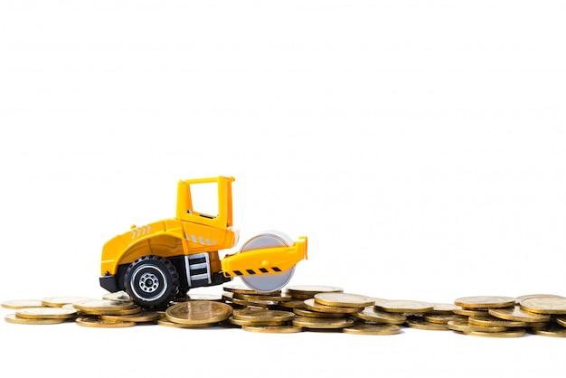 Mini rullo compressore con pila di monete d'oro, isolato su bianco