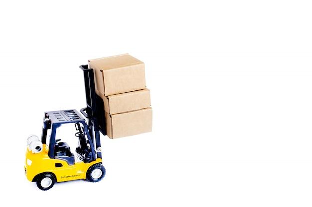 Mini scatole di cartone del carico del carrello elevatore a forcale isolate su fondo bianco. idee di gestione della logistica e dei trasporti e concetto commerciale di industria.