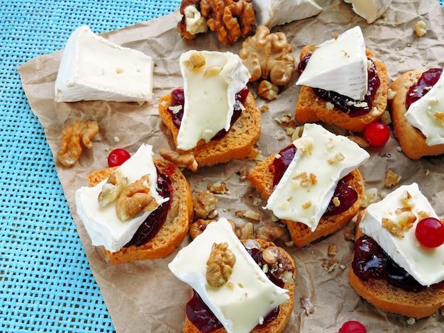 Mini toast con marmellata di mirtilli rossi, camembert e noci.