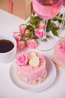 Mini torta con glassa rosa, bellissime rose, tazza di caffè, bicchiere di vino rosa sul tavolo bianco.