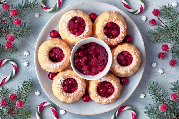 Mini torte ad anello con zucchero a velo sul tavolo luminoso con rametti di abete, bacche e bastoncini di zucchero