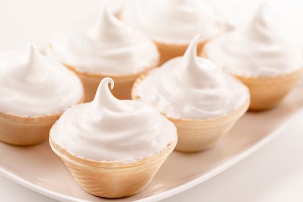 Mini torte con crema di formaggio su uno sfondo bianco