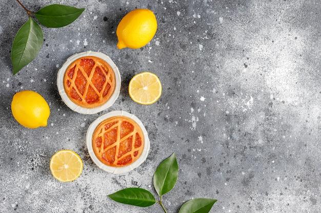 Mini torte deliziose al limone con limoni freschi, vista dall'alto