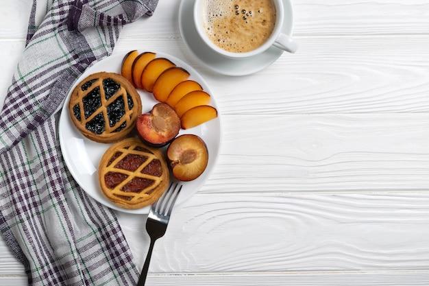 Mini torte di frutta con ripieno diverso e prugne fresche servite con caffè