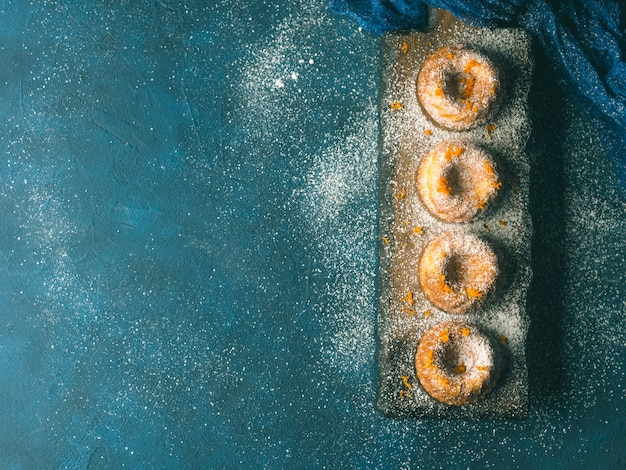 Mini torte per fagottini con zucchero a velo a scaglie d'arancia su tavola blu scuro e servizio. vista dall'alto. alimento dolce di natale di festa tonificato