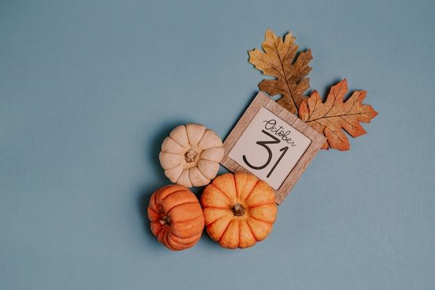 Mini zucche e data di calendario arancio nel telaio di legno