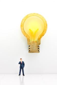 Miniatura dell'uomo d'affari che pensa con l'idea della lampada