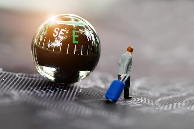 Miniatura dell'uomo d'affari con bagaglio che cammina sulla mappa e sulla bussola di mondo