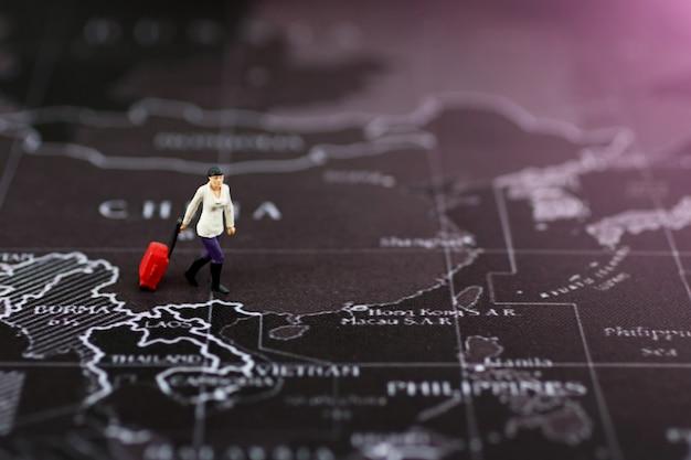 Miniatura della donna di affari con bagaglio che cammina sulla mappa di mondo