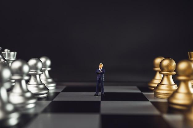Miniatura di leader nel mezzo del concetto di squadra o personale. boss in piedi davanti a scacchi d'oro sulla scacchiera con scarsa luminosità.