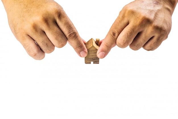 Miniatura di legno della casa con la mano su fondo bianco