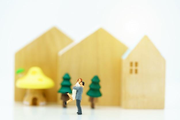 Miniatura di persone amante in piedi con la casa