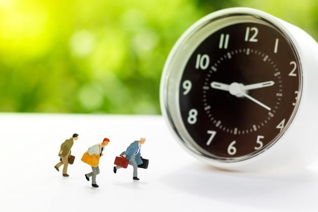 Miniatura di persone che corrono vanno in ufficio con l'orologio