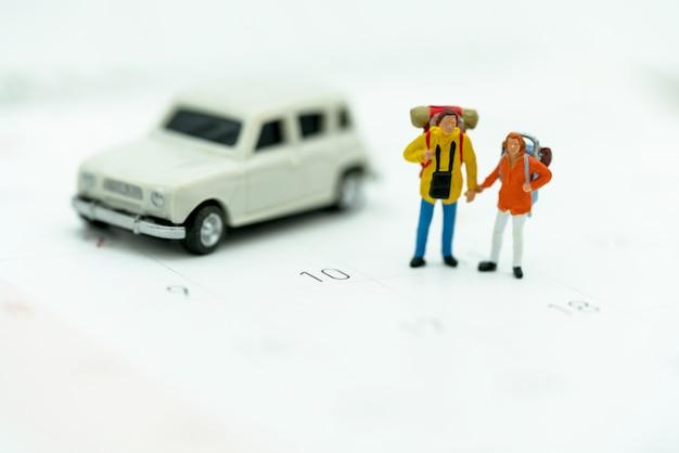 Miniatura di turisti con zaini in piedi sul calendario di viaggio