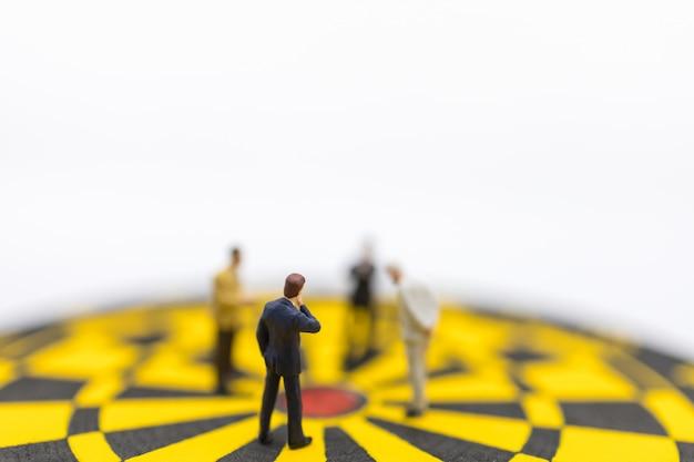Miniatura di uomo d'affari in piedi e guardando al centro del bersaglio per le freccette giallo e nero