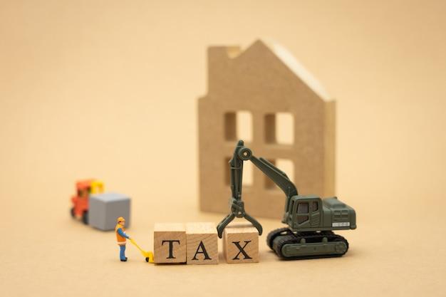 Miniatura operaio edile in piedi con la parola di legno fiscale