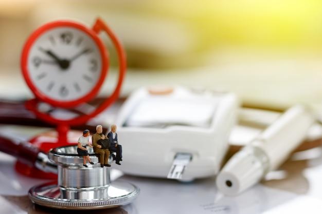 Miniatura persone sedute su stetoscopio e glucometro del diabete con orologio.
