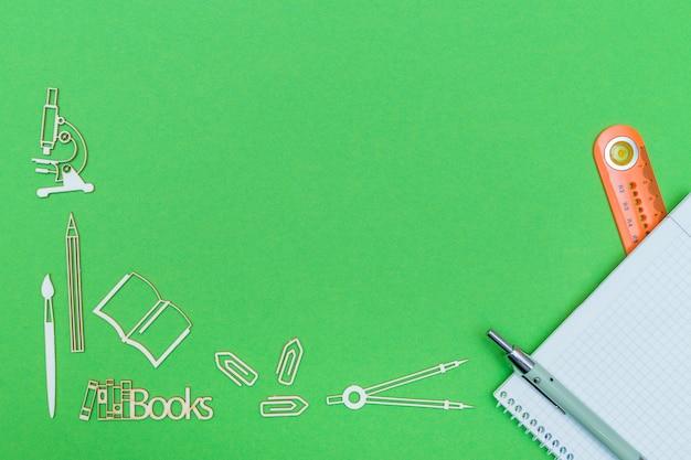 Miniature e taccuino di legno dei rifornimenti di scuola con il righello e la penna su fondo verde