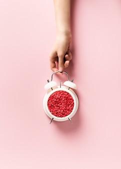 Minimalis pastello di concetto di giorno di san valentino, tempo di regalo, sveglia e mano