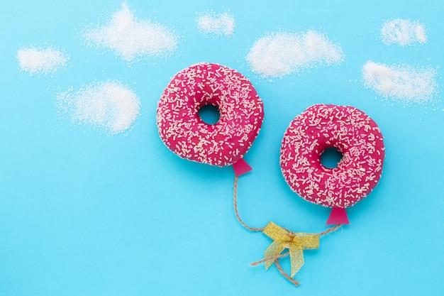 Minimalismo alimentare creativo. ciambella su sfondo blu, ciambella a forma di palloncino nel cielo, vista dall'alto