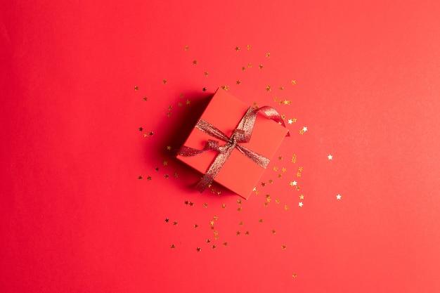 Minimo concetto di capodanno. composizione creativa del contenitore di regalo con l'arco della decorazione dell'oro su fondo rosso. creativo design piatto, vista dall'alto.