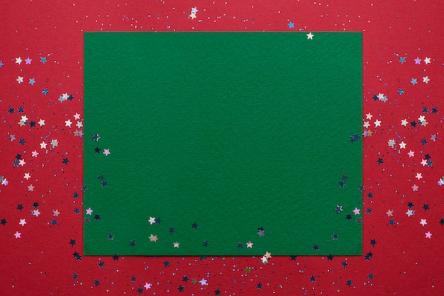 Minimo concetto di natale. carta ruvida verde su sfondo rosso, cosparsa di scintillii e stelle.